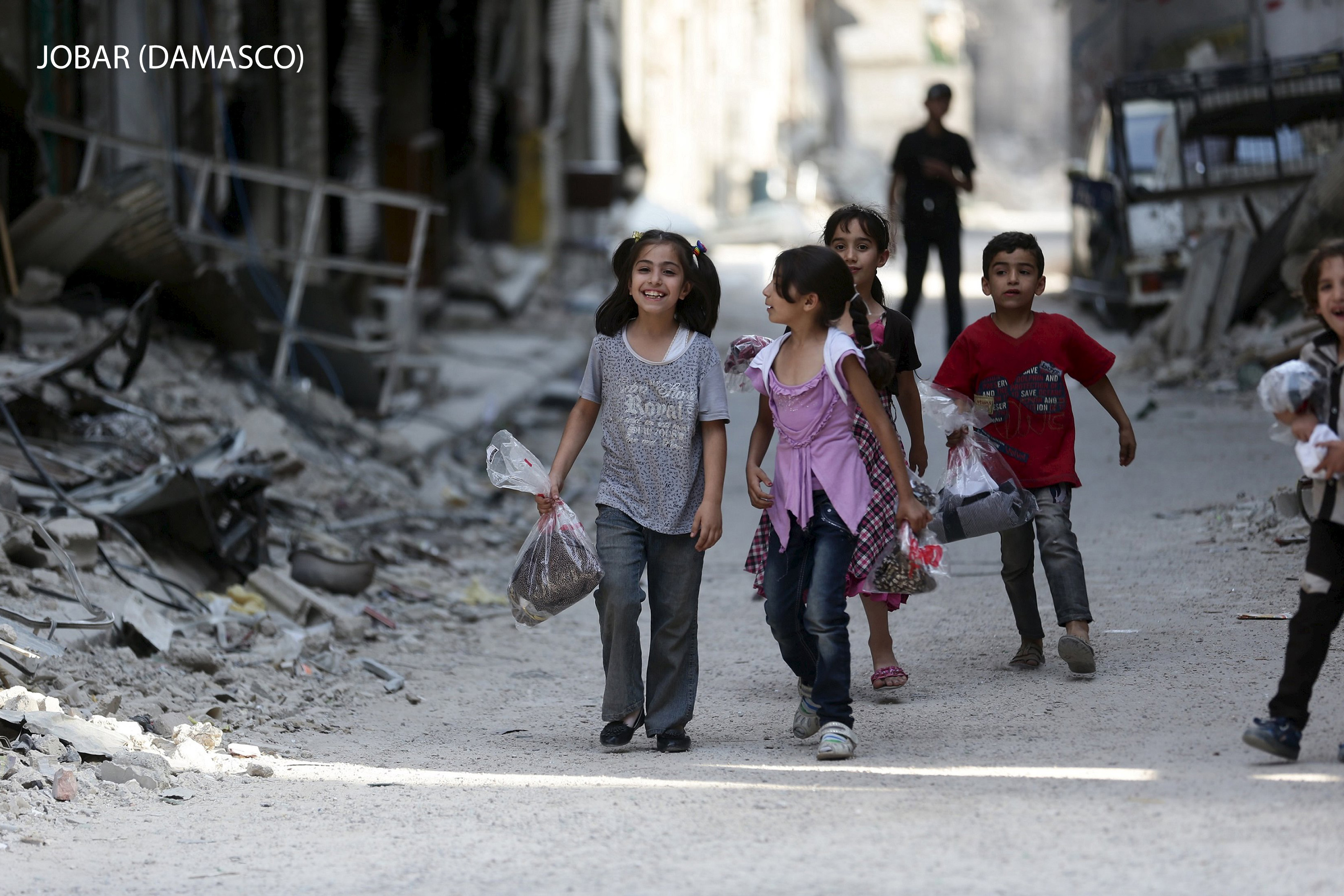 Children carry bags of new clothes ahead of the Eid al-Fitr holiday marking the end of Ramadan in Jobar, a suburb of Damascus, Syria July 15, 2015. Picture taken July 15, 2015. REUTERS/Bassam Khabieh