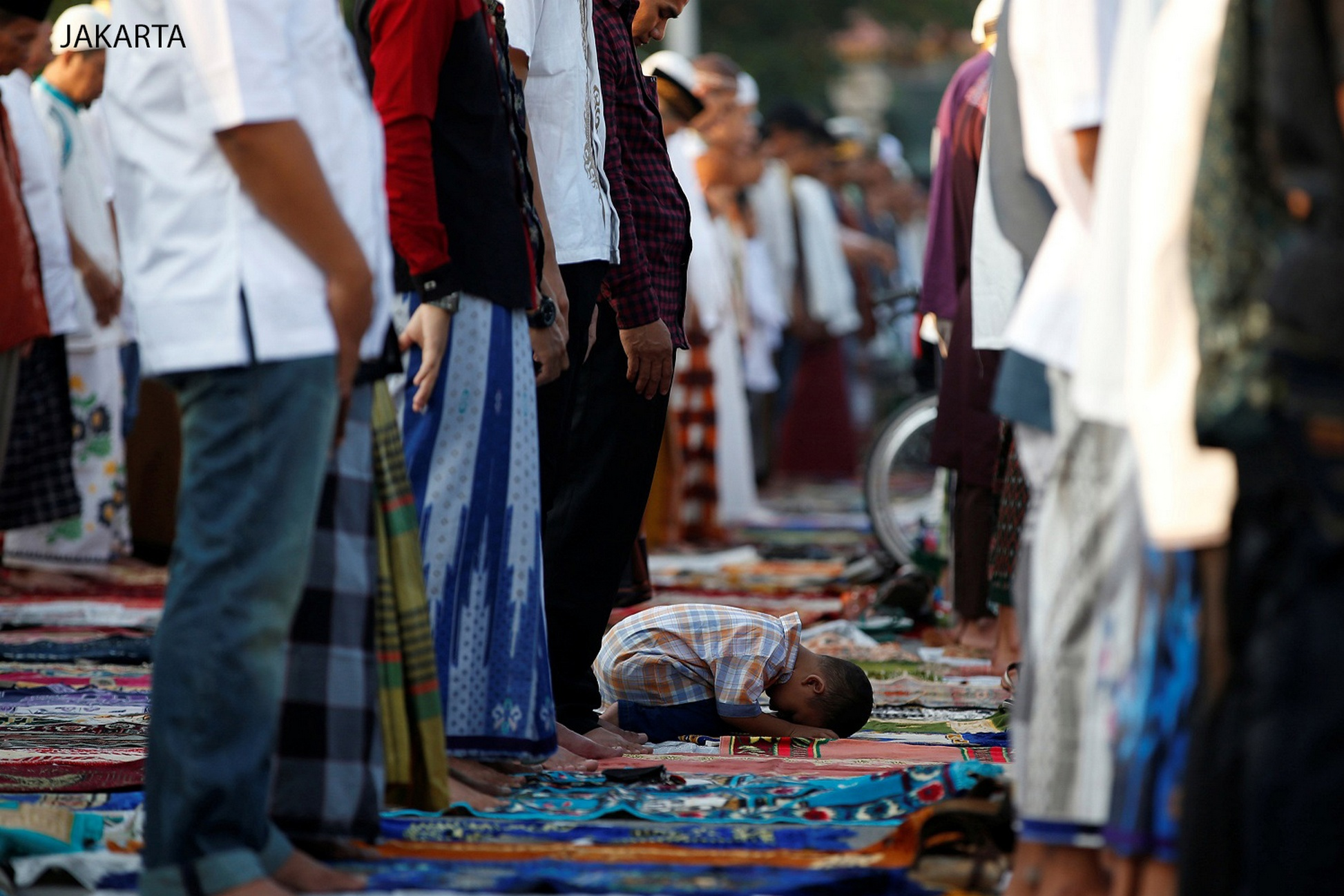 A child attends Eid al-Fitr prayers to mark the end of the holy fasting month of Ramadan at Sunda Kelapa port in Jakarta, Indonesia July 6, 2016. REUTERS/Darren Whiteside