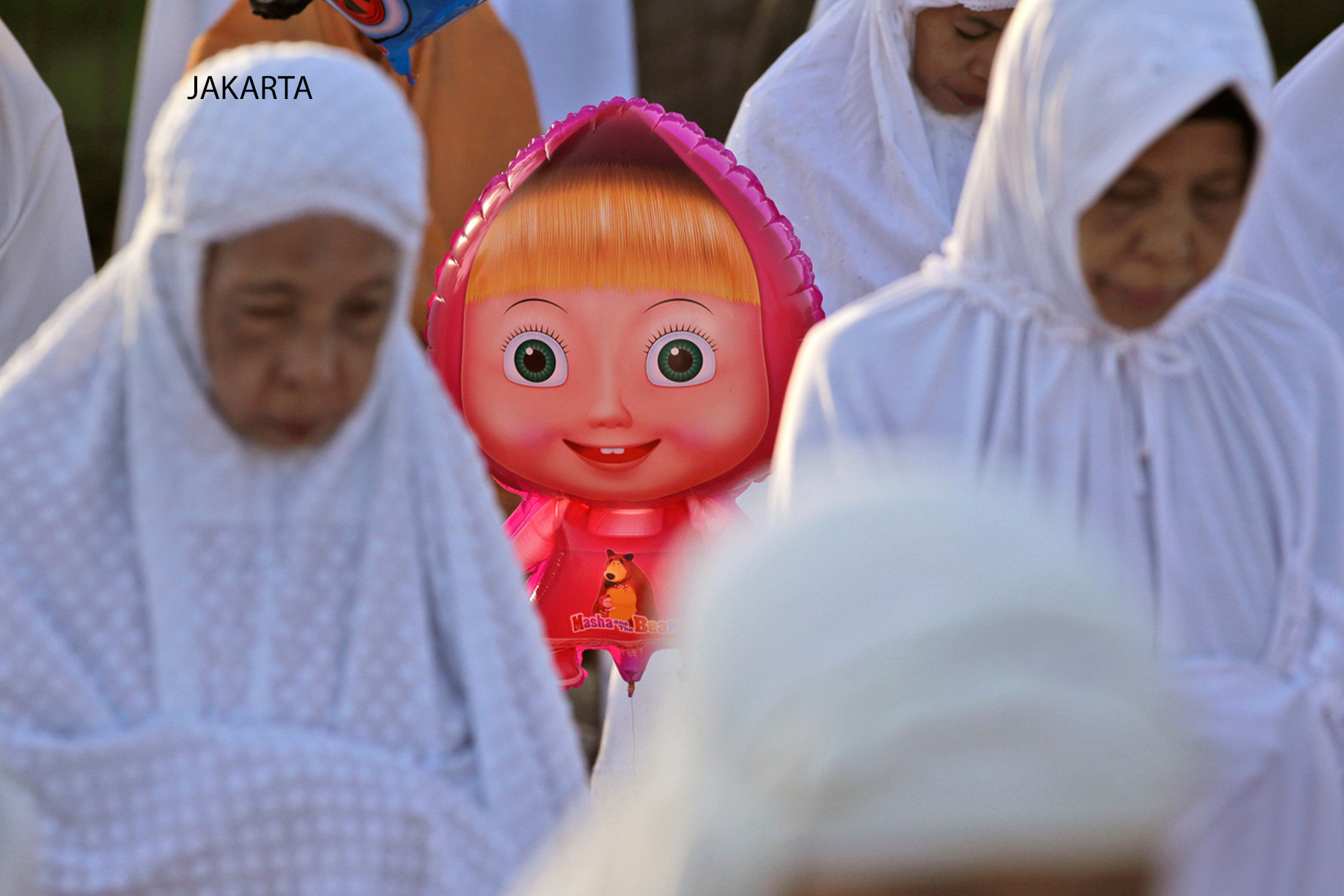 "A balloon of Russian cartoon character '""Masha"" peeks through Musim women performing an Eid al-Fitr prayer to mark the end of the holy fasting month of Ramadan at Sunda Kelapa port in Jakarta, Indonesia, Friday, July 17, 2015. (AP Photo/Dita Alangkara)"