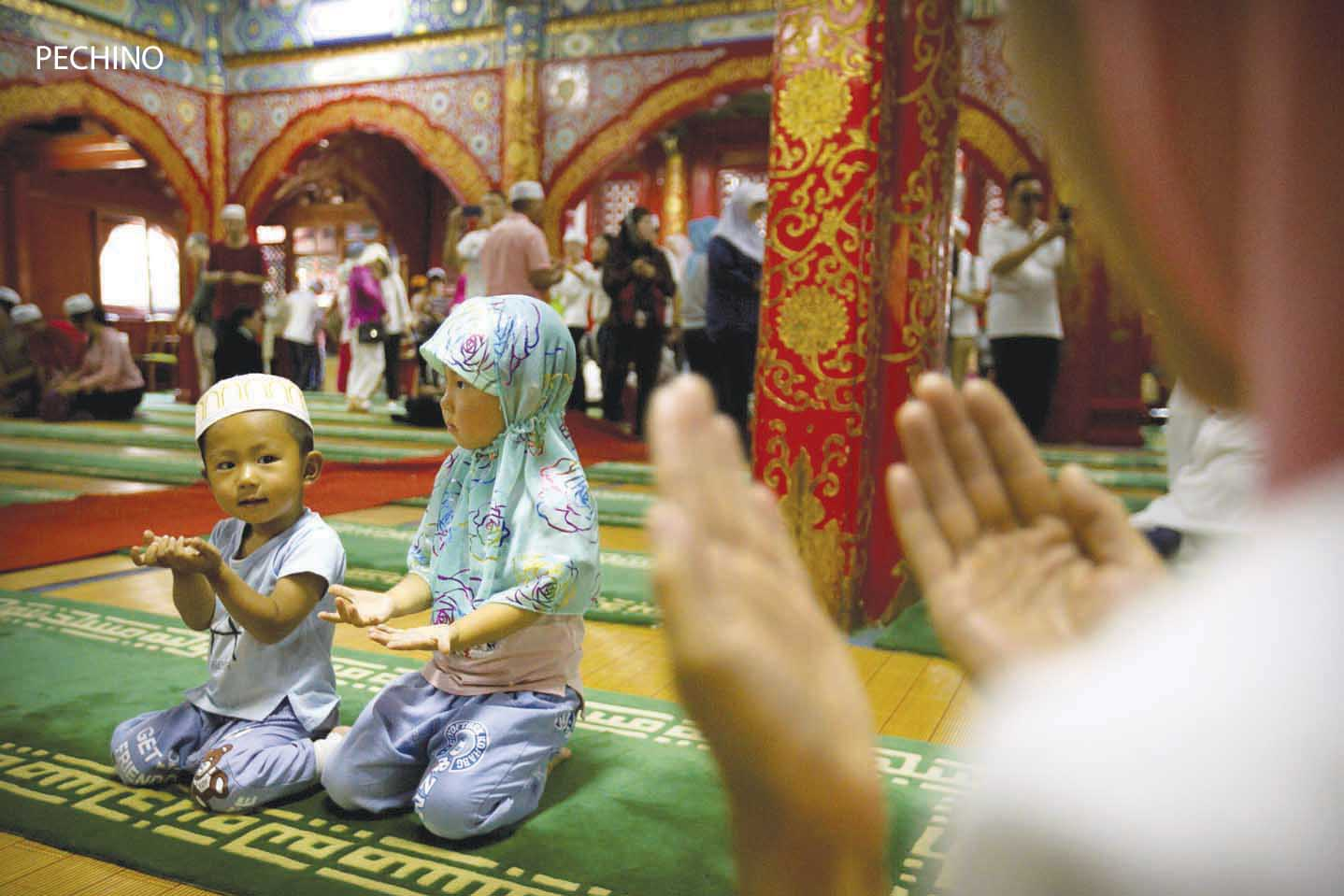 Beijing : Children kneel inside the historic Niujie Mosque after Eid al-Fitr prayer services in Beijing, Monday, June 26, 2017. Although much of the Muslim world celebrated Eid al-Fitr, which marks the end of the holy fasting month of Ramadan, on Sunday, Muslims in China observed the holiday on Monday. AP/PTI(AP6_26_2017_000068B)